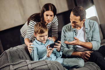 Stop playing. Loving young parents standing near their pre-teen son and convincing him to put down the phone, while the boy refusing, being stubborn