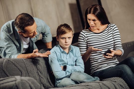 Clear explanation. Strict young parents telling their son about the drawbacks of binge-playing on the phone while the boy, scolding him, while the boy looking offended