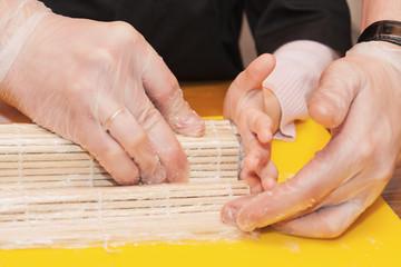 Children prepare sushi rolls. Master-class in the restaurant. Selective focus