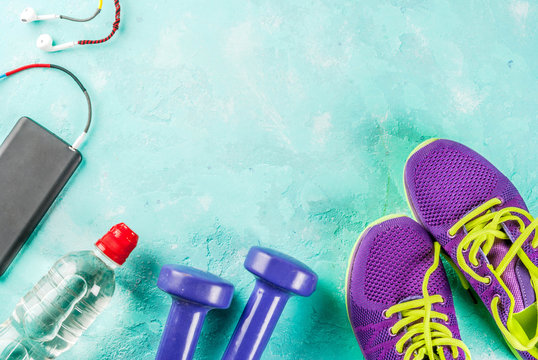 Sports, fitness concept. Running sneakers, water bottle, headphones, dumbbells, smartphone, on a light blue background top view copy space