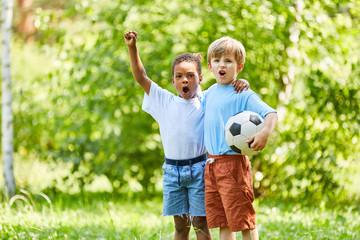 Multikulturelle Jungen als Freunde mit Fußball