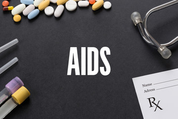 AIDS written on black background with medication
