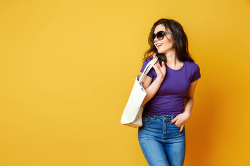 Beautiful young woman in sunglasses, purple shirt, blue jeans posing with bag on the wonderful yellow background