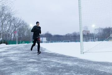 Image of sporty man running at stadium in winter