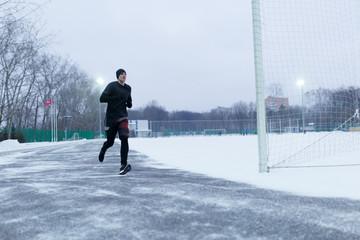 Image of sporty man running at stadium in winter