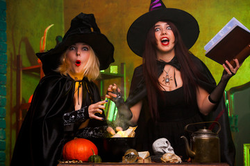 Photo of two witches with book of incantations in dark room