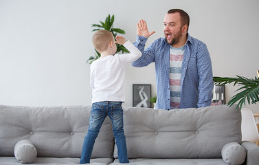 Family picture of young son standing on couch doing handshake with father