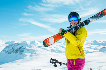 Image of girl wearing helmet, mask with skis on her shoulder