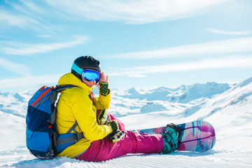 Photo of woman in helmet with backpack sitting on snow with snowboard
