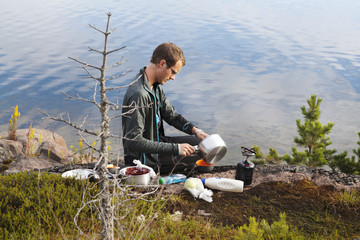 Young man cooking on riverbank in High Coast, Sweden