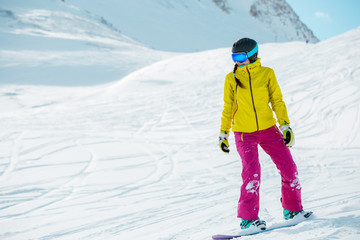 Photo of athlete girl wearing helmet in sports clothes snowboarding