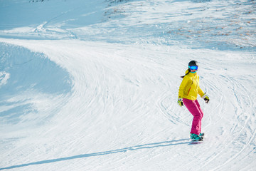 Image of sports woman snowboarding from mountain slope