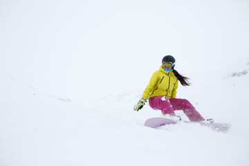 Picture of athlete girl in helmet with developing hair, snowboarding from mountain slope