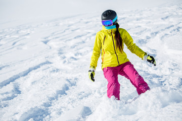 Picture of athlete girl in helmet and mask, snowboarding from snowy mountain slope