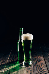shining glass and bottle of green beer on wooden table, st patricks day concept