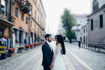 Wedding portrait of the attractive young couple tenderly holding hands in the town street.
