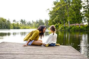 Mother and daughter on pier beside lake in Friseboda, Sweden