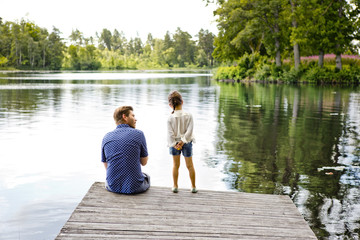 Father and daughter on pier beside lake in Friseboda, Sweden