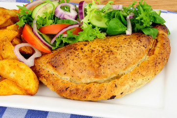 Pasty and potato wedges meal with fresh salad isolated on a white background