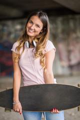 Smiling girl holding skateboard