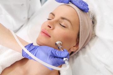 Peeling tlenowy. Kobieta w salonie kosmetycznym podczas zabiegu pielęgnacyjnego