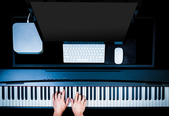 male musician hands playing piano for recording on desktop computer, copy space on screen