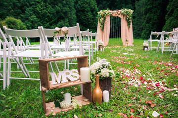 Beautiful place made with wooden square and floral roses decorations for outside wedding ceremony in green park. Rows of many empty wooden chairs ready for guests. Wedding settings at scenic place.