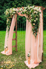 Beautiful place made with wooden square and floral roses decorations for outside wedding ceremony in green park. Wedding settings at scenic place. Vertical color photography.