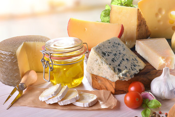 Various types of cheeses presented on wooden table in kitchen