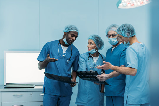 four multiethnic surgeons talking about patient x-ray in operating room