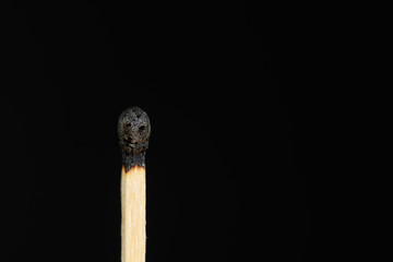 Match with the burned head showing a smiley on a black background closeup