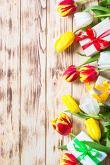 Tulips flower and present box on wooden table.