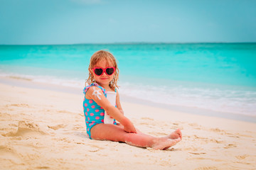 sun protection on beach- little girl applying sunblock cream on shoulder