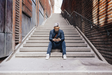 Man with smart phone sitting on staircase in Sweden