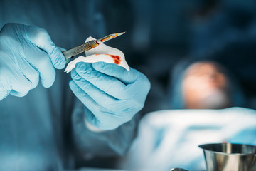 cropped image of surgeon cleaning scalpel from blood