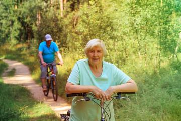 happy senior couple riding bikes in nature