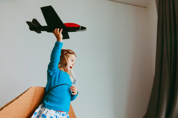 little girl with pilot glasses and wings play fly at home