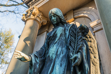 Angel Statue between Pillars is Protecting, Guarding and Comforting on a cemetery/graveyard