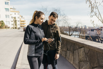Couple on street looking at smart phone in Stockholm, Sweden
