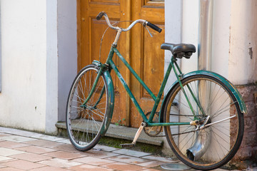 Old bicycle in front of the house door, traditional mode of transportation for healthy life