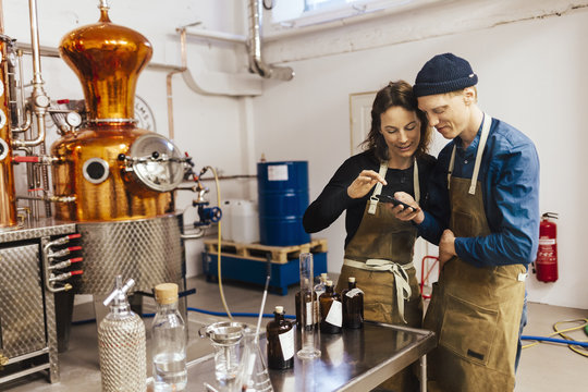 Young couple using smartphone at gin distillery