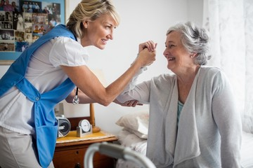 Nurse helping senior woman to stand up