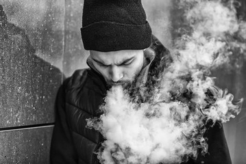 Vape man. Portrait of a handsome young white guy in black waistcoat and modern cap vaping an electronic cigarette opposite the futuristic urban background. Black and white.