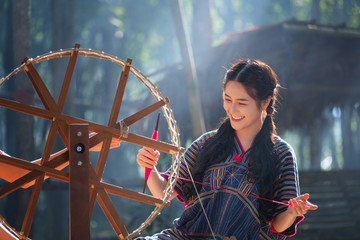 Thai Beautiful women smile in karen suit spinning thread on a bamboo mat in a forest nature local village Thailand