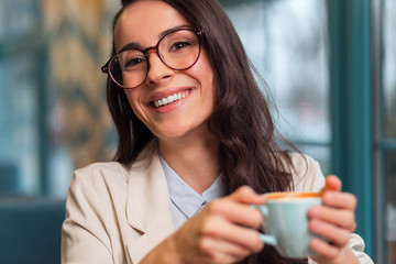 Nice day. Merry positive beautiful woman posing on the blurred background while grinning and carrying cup of coffee