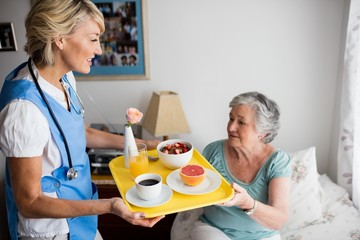 Nurse giving food to a senior woman
