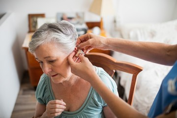 Nurse putting hearing aid to a senior woman