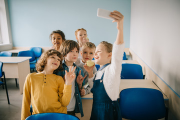 group of happy kids taking selfie at school classroom