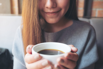 Closeup image of Asian woman smelling and drinking hot coffee with feeling good in cafe