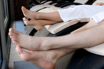 close-up partial view of barefoot couple in bathrobes resting in spa calon
